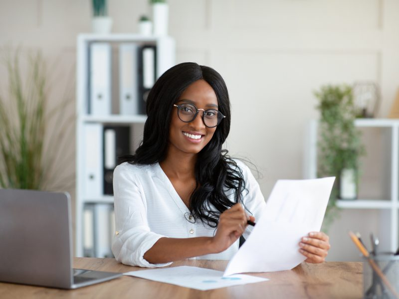 Beautuful black business lady working with documents at desk in office. African American female entrepreneur looking frough important contract or agreement at her workplace